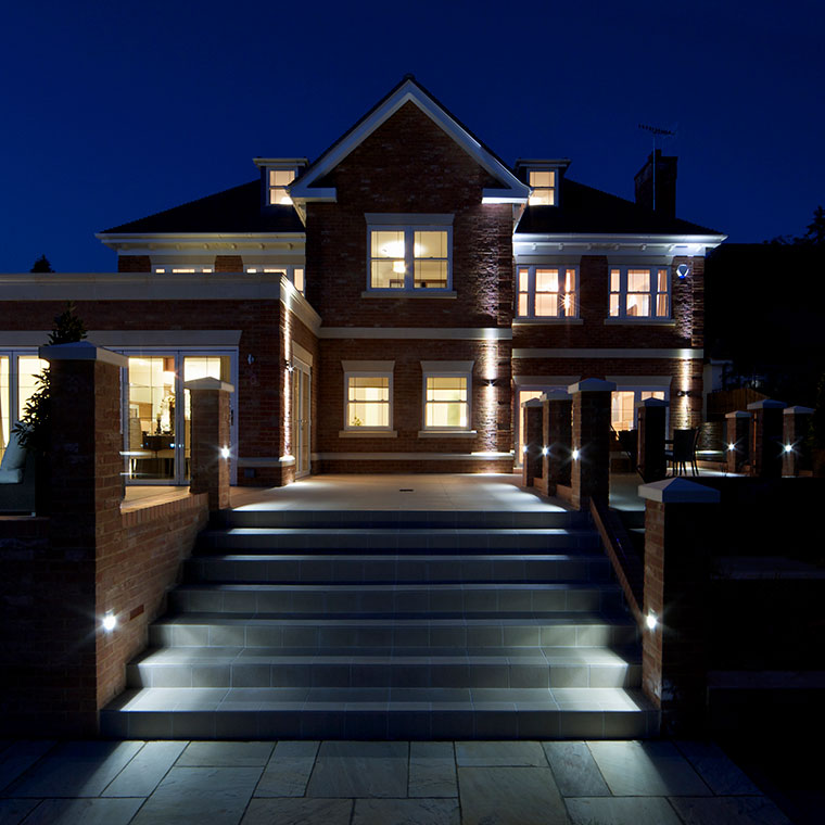 Night photo of front sidewalk leading up to a beautifully lighted upscale home.
