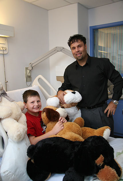 George Lou Karmiris presents stuffed animals to kids in hospital bed at BGH.