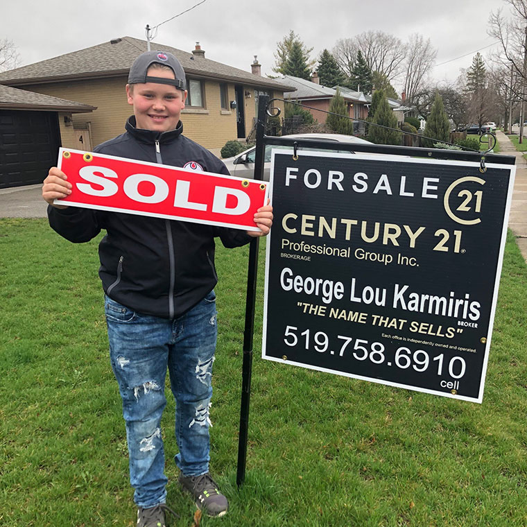 Teenager holding sold sign on front lawn.