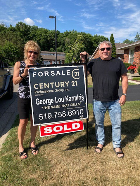 Clients of George Lou Karmiris standing with the sold sign.