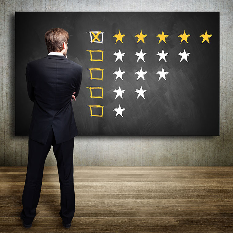 Man standing in front of a blackboard with multiple star ratings from one to five.